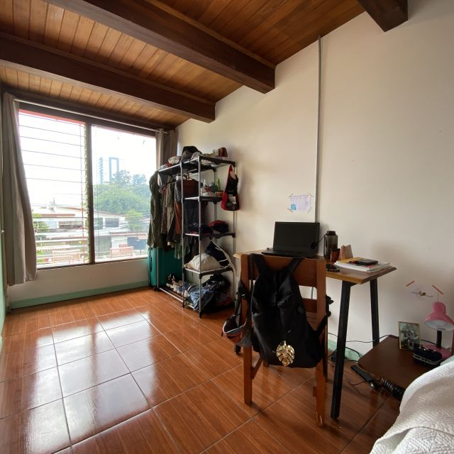 Blick in ein kleines Zimmer mit einem Schreibtisch, einem offenen Schrank und einem großen Fenster.