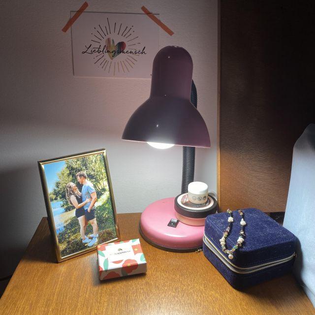 """Auf einem Nachttisch stehen ein Foto von einem Pärchen und eine Postkarte mit """"Lieblingsmensch"""" hängt an der Wand."""