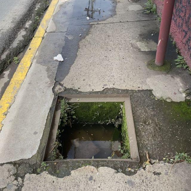 Ein Abwasserschacht auf dem Fßweg ohne Gullideckel.