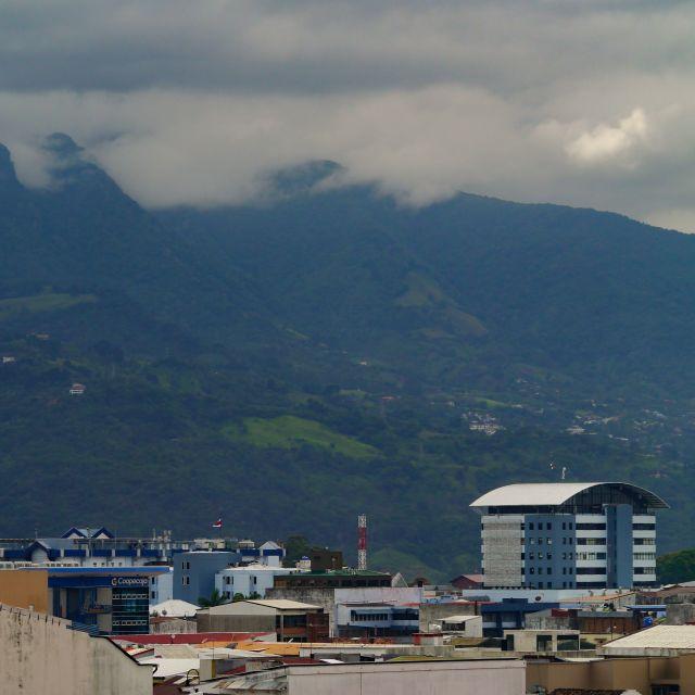 Blick auf bewaldete Berge vor einer Stadtkulisse.