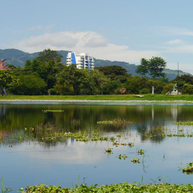 Ein See umgeben von Bäumen, durch die städtische bauten durchscheinen. Im Hintergrund bewaldete berge.