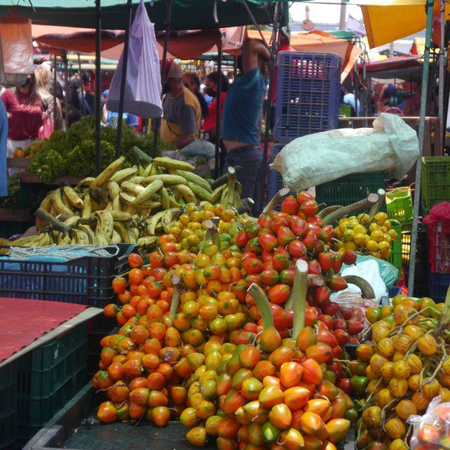 Staudenweise orange-gelbe Früchte liegen an einem Verkaufsstand