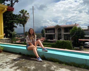 Carla sitzt am Rand einer Terrasse, und hinter ihr sieht man San Jose.