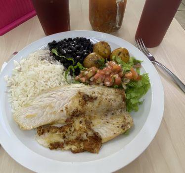 Ein Teller mit Reis, Bohnen, Fisch und Gemüse.
