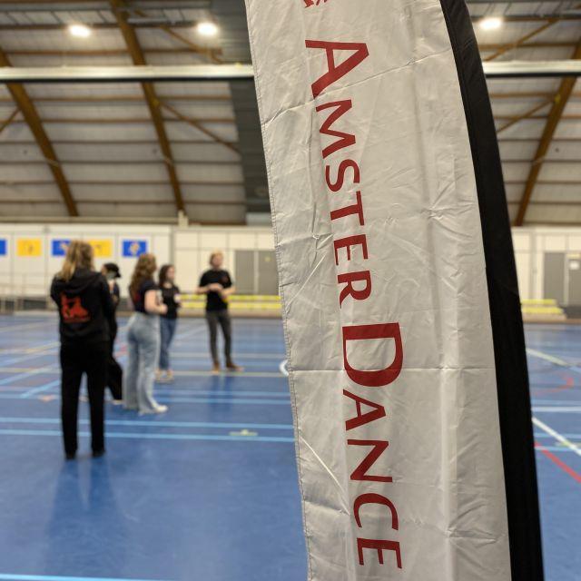 Man sieht einen Banner auf dem AmsterDance steht. Der Banner steht in einer Turnhalle. Im Hintergrund sieht man fünf Menschen, die miteinander sprechen.