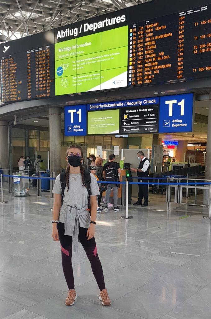 Franziska vor der Abflugtafel am Flughafen in Stuttgart
