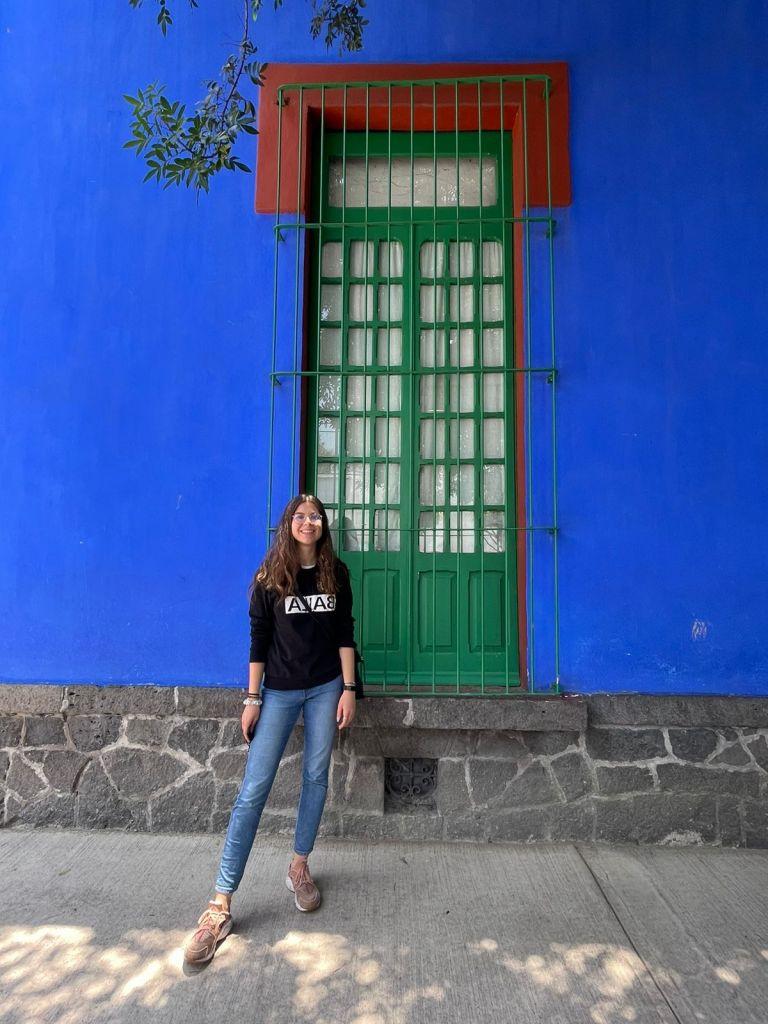 Franziska vor blauem Haus mit einem großen grünen Fenster