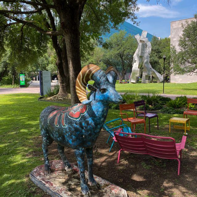 Die Statue eines bunt bemalten Widders steht im Park des Campus im Vordergrund, im Hintergrund ist eine andere Statue zu sehen.