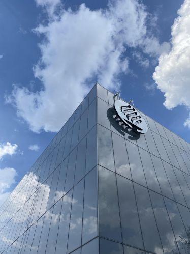 Gebäude mit dem Logo der Universität, Wolken spiegeln sich im Gebäude
