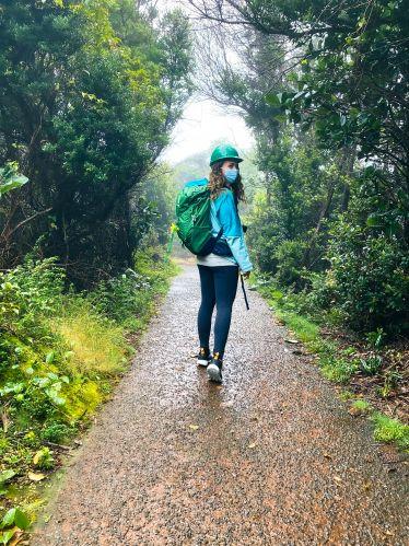 Carla steht mit Regenjacke und Trekkingrucksack in einem nebligen Wald