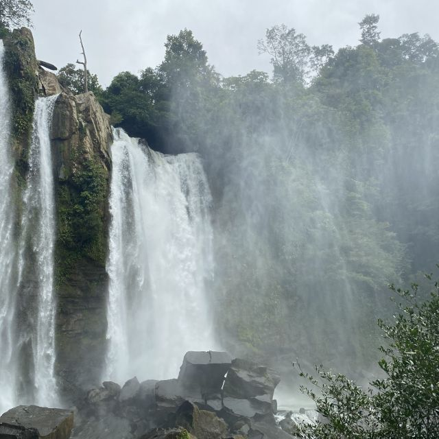 Hohe, breite Wasserfälle ergießen sich in ein Becken, drumherum tropischer Wald.