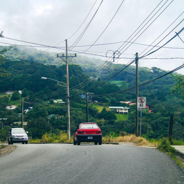 Eine asphaltierte, wenn auch unmarkierte Straße führt in grün bewaldete Berge.