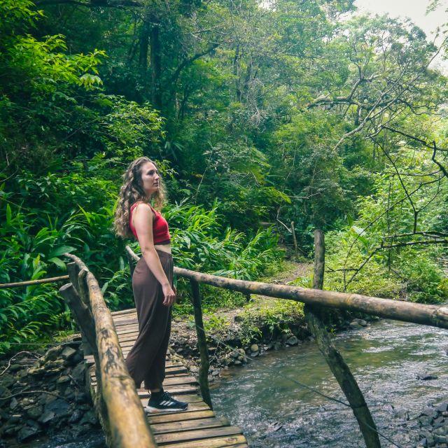 Carla steht in einem roten Top und einer langen Hose auf einer schmalen Holzbrücke über einen kleinen Bach.