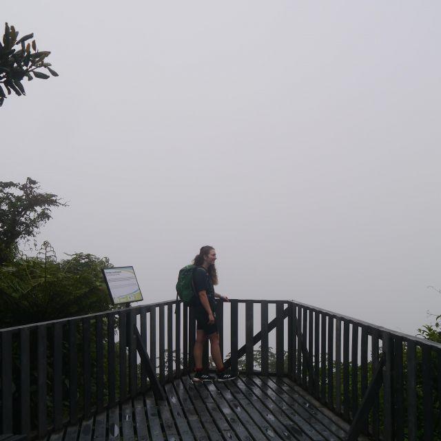 Carla steht vorm Geländer einer Aussichtsplattform, hinter ihr ist eine weiße Wolkenwand zu sehen.
