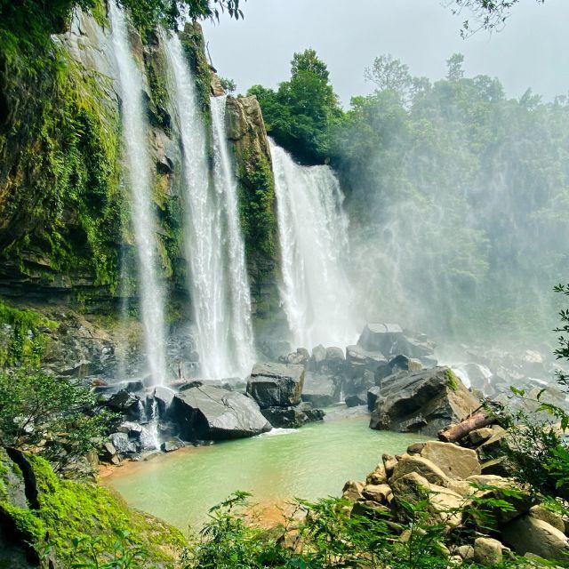 Ein großer Wasserfall erstreckt sich über mehrere Meter und ergießt sich im freien Fall in ein kleines türkises Becken.
