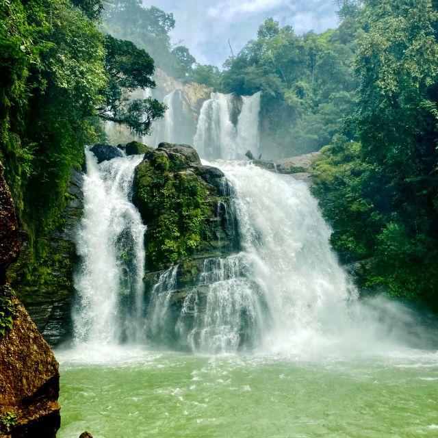 Ein kleineren Wasserfall ergießt sich über mehrere Stufen in ein großes, tiefes Becken.