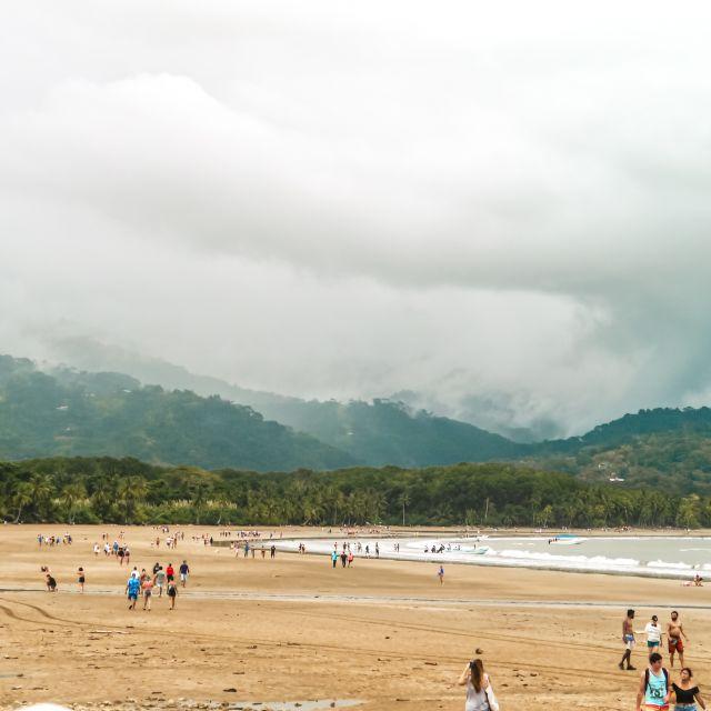 Ein breiter Strand mit vielen Leuten.