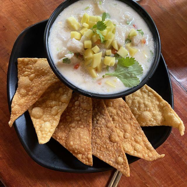 Eine Schüssel mit Fischstücken in einer milchigen Soße mit Ananasstücken obendrauf, serviert mit Tortillachips.