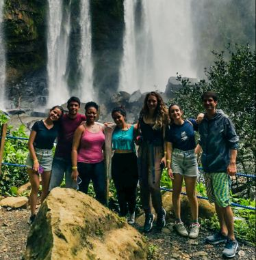 Sieben junge Leute aus verschiedensten Teilen der Welt stehen vor einem Wasserfall.