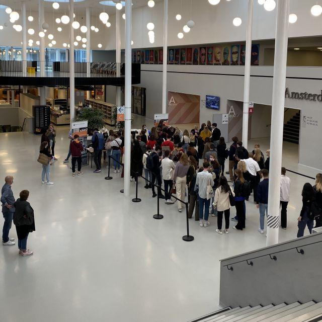 Man sieht viele Stundent:innen in der großen Eingangshalle der Universität in einer Schlange warten.