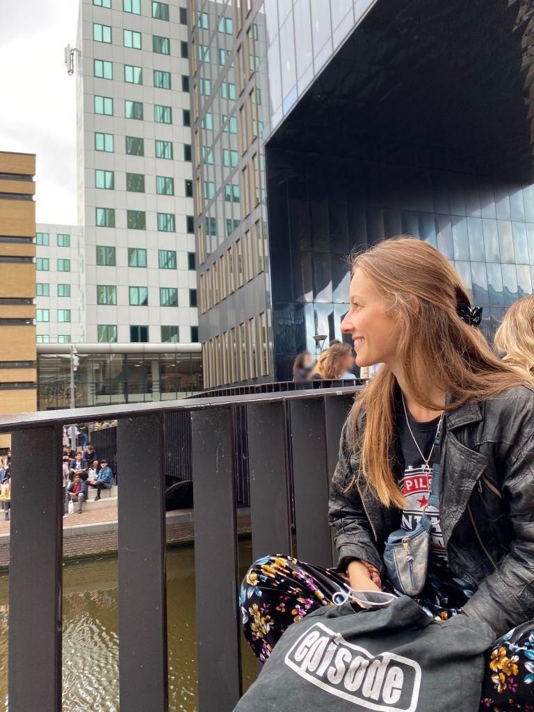 Ich sitze auf einer Bank auf der Brücke beim Campus. Im Hintergrund sieht man andere Studierende.