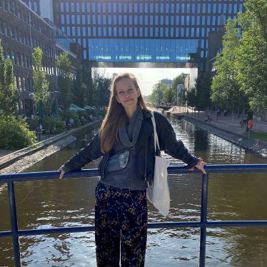 Ein Mädchen steht auf einer Brücke vor dem Universitätscampus. Die Sonne scheint.