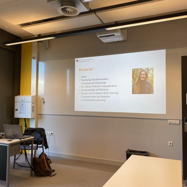 Man sieht eine PowerPoint-Folie. Ich stelle mich darauf auf Niederländisch vor. Man sieht ein Foto von mir.