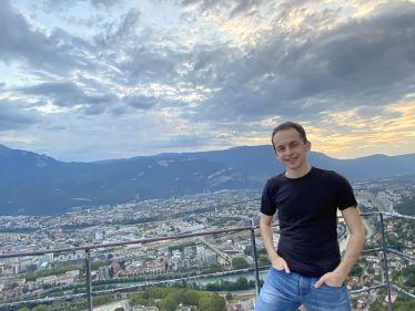 Mann lächelt, Berge und Stadt Grenoble im Hintergrund