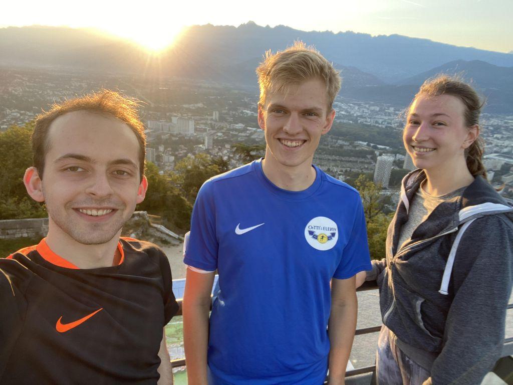 Drei junge Menschen in Sportklamotten vor einem Sonnenaufgang