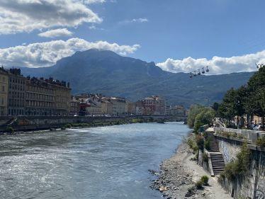 Fluss, im Hintergrund Berge und eine Seilbahn