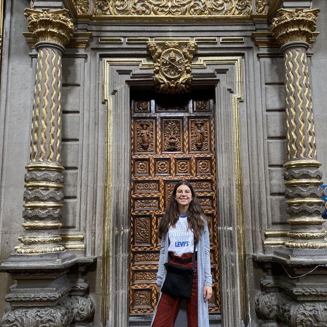 Franziska in der Kathedrale von Puebla vor einer verzierten Tür mit zwei Säulen.