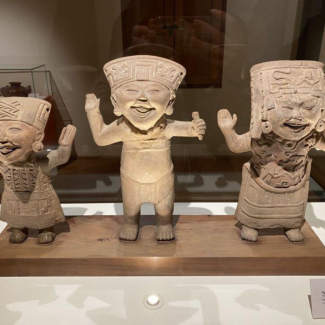 Drei Figuren mit einem starken lächelnden Gesicht.