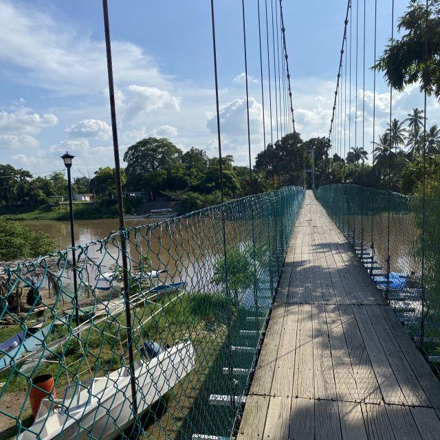 Eine lange Hängeseilbrücke, die über den Fluss führt.
