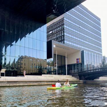 Man sieht ein orangenes Kanu auf einem Kanal. Der Kanal geht durch den Campus der Universität von Amsterdam. Links vom Kanal kann man große, gläserne Unigebäude erkennen.