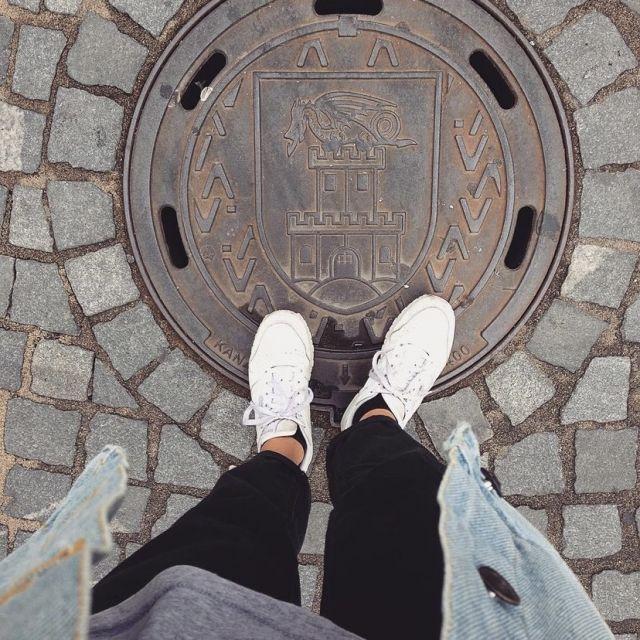 Von oben auf einen Gullideckel fotografiert, außerdem sieht man die Beine und Schue der fotografierenden Person.
