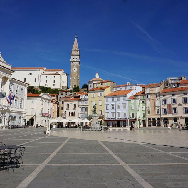 Ein Großer Platz umgeben von pastellfarbenen Häusern. Im Hintergrund ein Kirchturm.
