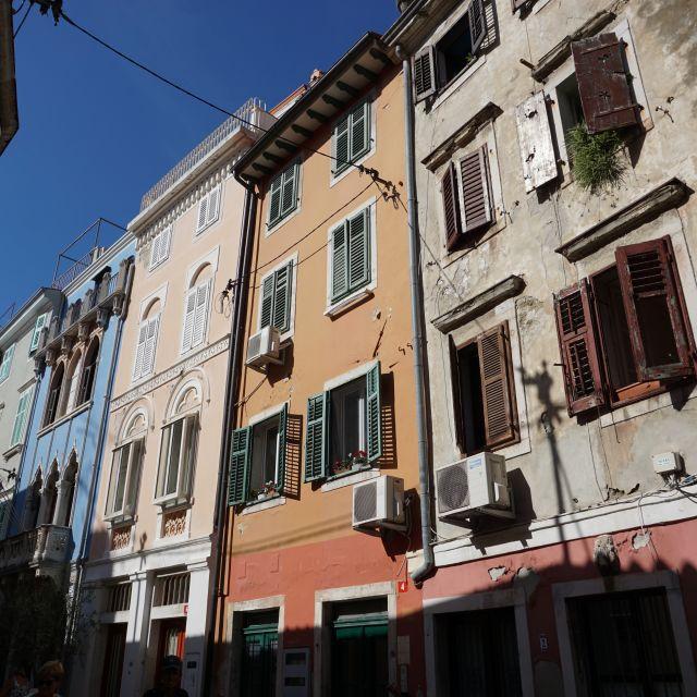 Häuserreihe aus bunten Häusern mit Fensterläden.