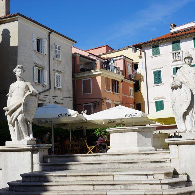 Zwei Statuen stehen links und rechts von einer Treppe. Im Hintergrund alte Häuser.