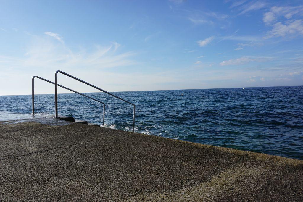 Betonfläche, von der eine Treppe ins Meer führt.