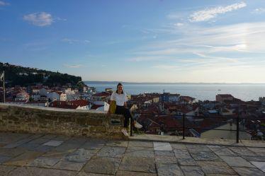 Tamara sitzt in der Mitte des Bildes auf einer kleinen Mauer. Im Hintergrund ist eine Stadt und das Meer zu sehen.