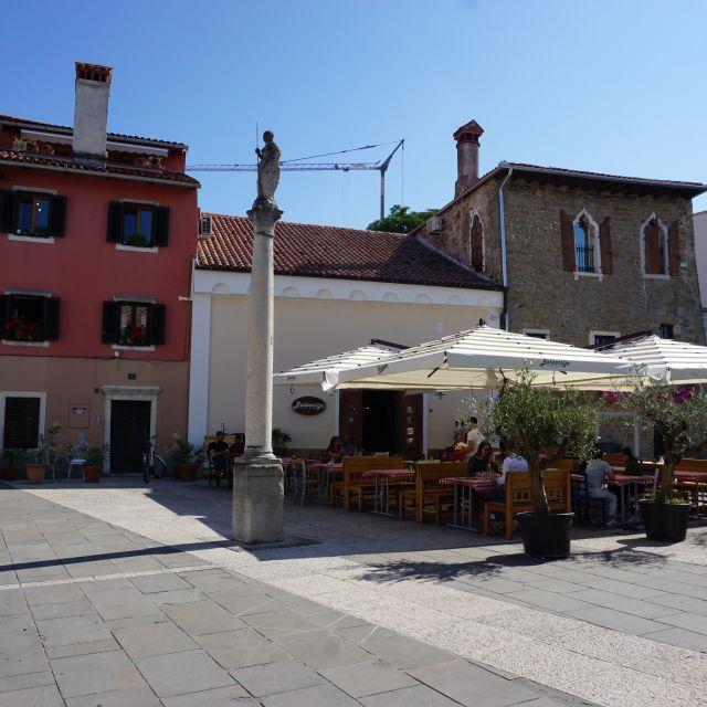 Platz mit Statue. Rechts im Bild eine Restaurantterrasse mit großen Sonnenschirmen.