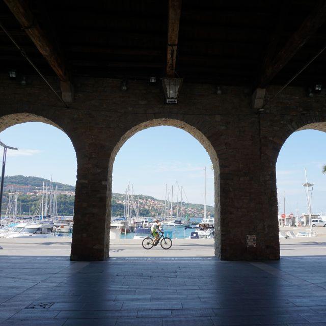 Drei große Bögen, durch die man hindurchblickt. Es ist der Hafen zu sehen und in der Mitte fährt ein Radfahrer.