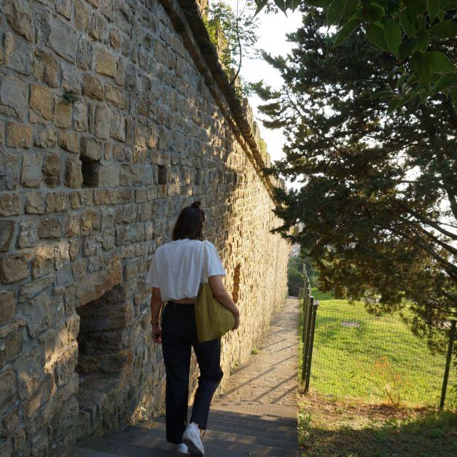Tamara geht eine Treppe hinunter. Links ist eine alte Steinmauer zu sehen.