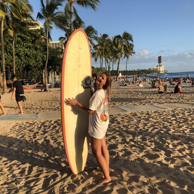 Victoria am Waikiki Beach mit einem Surfboard in der Hand