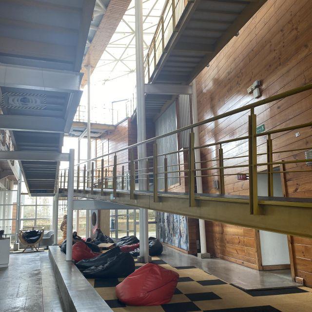 Ein großer heller Raum mit einer Treppe, darunter Sitzkissen.