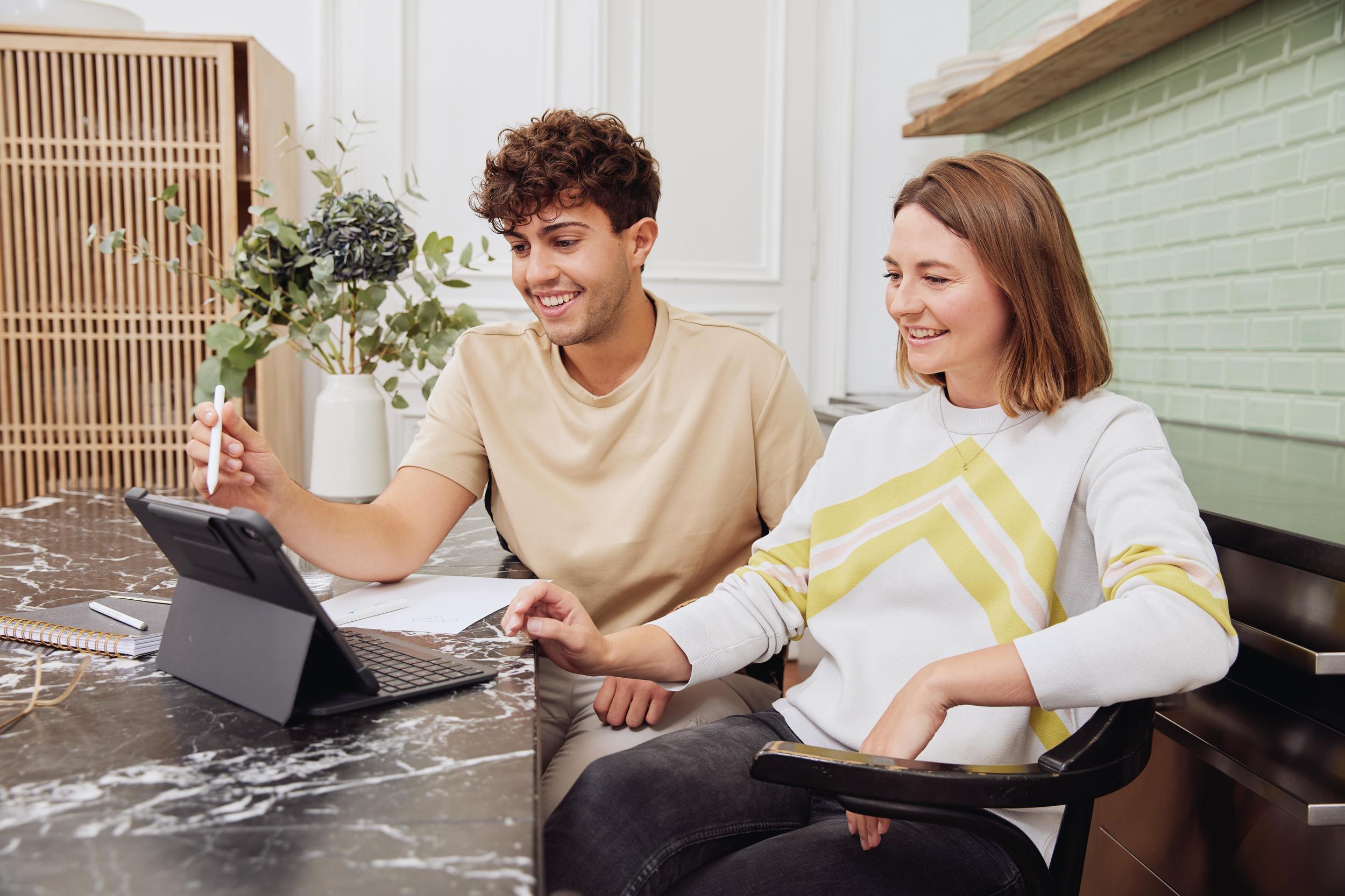 Frau und Mann sitzen vor Laptop und informieren sich zu Praktika im Ausland