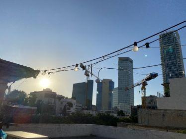 Dachterrasse mit Wolkenkratzern von Tel Aviv im Hintergrund. Eine Lichterkette und die untergehende Sonne.