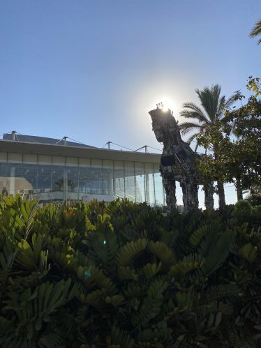 """Im Vordergrund sind Pflanzen zu sehen, rechts im zweiten Drittel die Skulptur """"Cyber Horse"""". Rechts von der Skulptur sind Palmen und die Sonne und links ein Auditorium."""