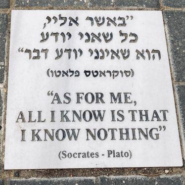 """Eine Tafel auf dem Boden mit der Inschrift """"As for me, all I know is that I know nothing"""" (Socrates-Plato) in Hebräisch und Englisch."""