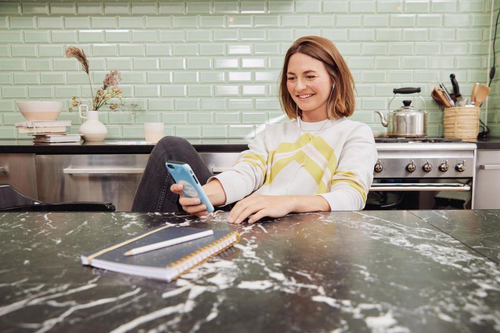 Frau sitzt am Tisch mit Handy